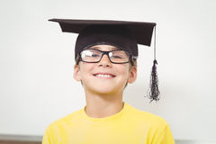 Smiling pupil with mortar board and glasses Royalty Free Stock Image