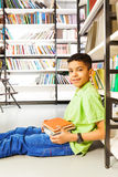 Smiling pupil with pile of books sitting on floor Royalty Free Stock Image