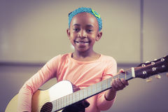 Smiling pupil playing guitar in a classroom Royalty Free Stock Photos
