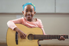 Smiling pupil playing guitar in a classroom Stock Photography