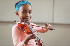 Smiling pupil playing violin in a classroom Stock Photos