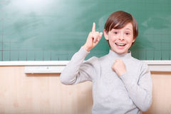 Smiling pupil pointing with his index finger Stock Images