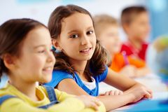 Smiling pupil. Portrait of a smiling pupil sitting next to her classmate Royalty Free Stock Images