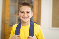 Smiling pupil with schoolbag in a classroom. Portrait of smiling pupil with schoolbag in a classroom in school Royalty Free Stock Photos