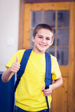 Smiling pupil with schoolbag doing thumbs up in a classroom Royalty Free Stock Photography