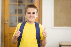 Smiling pupil with schoolbag doing thumbs up in a classroom Royalty Free Stock Images