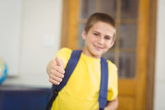 Smiling pupil with schoolbag doing thumbs up in a classroom Royalty Free Stock Photo
