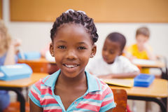 Smiling pupil sitting at her desk Royalty Free Stock Image