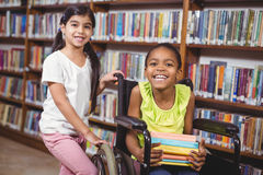 Smiling pupil in wheelchair holding books in the library Stock Photos
