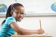 Smiling pupil working at her desk in a classroom. Portrait of smiling pupil working at her desk in a classroom in school Stock Image