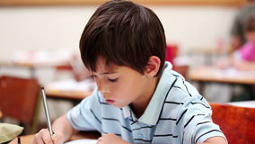 Smiling pupil writing on his notebook. In the classroom stock video footage