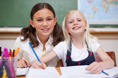Smiling pupils working together on an assignment Royalty Free Stock Photos
