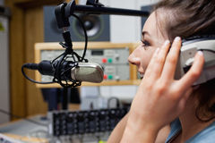 Smiling radio host speaking. Through a microphone Stock Image