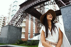 Smiling raven haired indian lady posing in backyard of  high-rise building Royalty Free Stock Photo