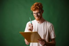 Smiling readhead bearded man in white tshirt holding folder and. Pen, over green background Stock Photo