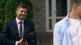 Smiling real estate agent looking at happy young family holding house key, rent