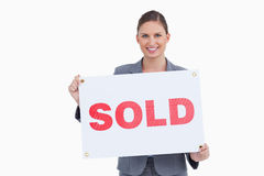 Smiling real estate agent presenting sold sign Stock Photo