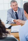 Smiling real estate agent shaking hands with his new buyer Stock Photos