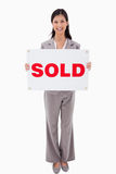 Smiling real estate agent with sold sign. Against a white background royalty free stock image