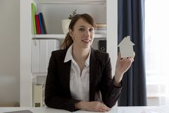 Smiling real estate saleswoman holding white model house. Real e Stock Photography