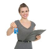 Smiling realtor holding clipboard and giving keys Stock Image