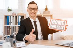 Smiling realtor shows thumbs up and holds sign with inscription. House for sale. stock photo