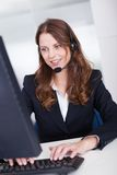 Smiling receptionist or call centre worker. Sitting typing at a computer while speaking into a headset with a microphone Stock Photography