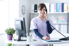 Smiling receptionist at the clinic. Young practitioner doctor working at the clinic reception desk, she is answering phone calls and scheduling appointments royalty free stock image