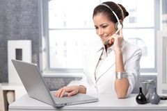 Smiling receptionist with headset. Portrait of smiling receptionist using laptop computer and headset at office desk royalty free stock photos