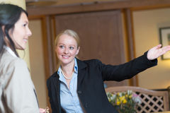 Smiling receptionist helping a hotel guest Royalty Free Stock Photo