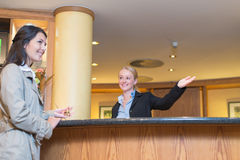 Smiling receptionist helping a hotel guest Stock Image