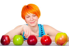 Smiling red hair woman choosing apple Royalty Free Stock Image
