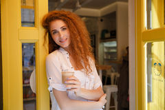 Smiling red hair woman standing and holding cup of coffee Royalty Free Stock Photography