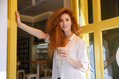 Smiling red hair woman standing and holding cup of coffee Stock Image