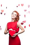 Smiling red-haired girl holding red heart Royalty Free Stock Photography