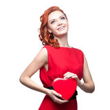 Smiling red-haired girl holding red heart Royalty Free Stock Photo