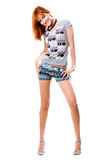 Smiling red-haired girl in a t-shirt and shorts Royalty Free Stock Photography