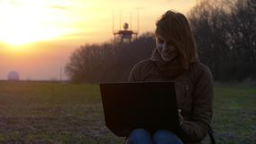 Smiling red-haired girl uses laptop near radar in field during sunset. Pretty red-haired girl uses laptop and laugh near radar and communication equipment stock video