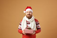 Smiling red-haired man with beard dressed in a red and white sweater with deer, white knitted scarf and a hat of Santa royalty free stock photography