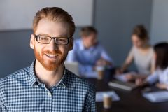 Smiling red-haired millennial business man in glasses looking at royalty free stock photography