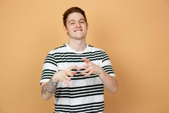 Smiling red-haired stylish guy in a striped shirt with tattoo on his hand is posing on the beige background in the royalty free stock image