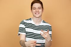 Smiling red-haired stylish guy in a striped shirt with tattoo on his hand is posing on the beige background in the stock images