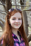 Smiling teen girl in a garden. Smiling red-haired teen girl in a garden stock image