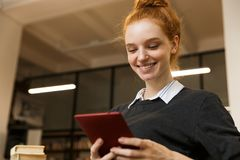 Smiling red haired teenage girl studying at the library stock photos