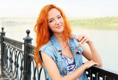 Smiling red haired women standing near river Royalty Free Stock Photos