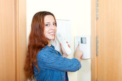 Smiling red-haired young woman talking on the house videophone. Indoors royalty free stock photo