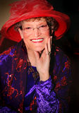 Smiling Red Hat Lady. An smiling senior lady wearing a large elaborate Red Hat and red and purple clothing. Shallow depth of field Stock Images