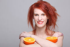 Smiling redhaired woman with orange half. In her hands Stock Photography