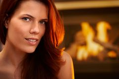 Smiling redhead beauty in front of fireplace Royalty Free Stock Photography