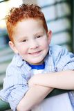 Smiling redhead boy. Young smiling redhead boy posing with his arms crossed Royalty Free Stock Photos